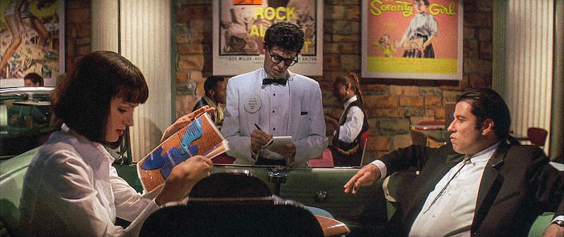 Buddy (Steve Buscem) is taking order from Mia (Uma Thurman) and Vincent (John Travolta) in 'Pulp Fiction'